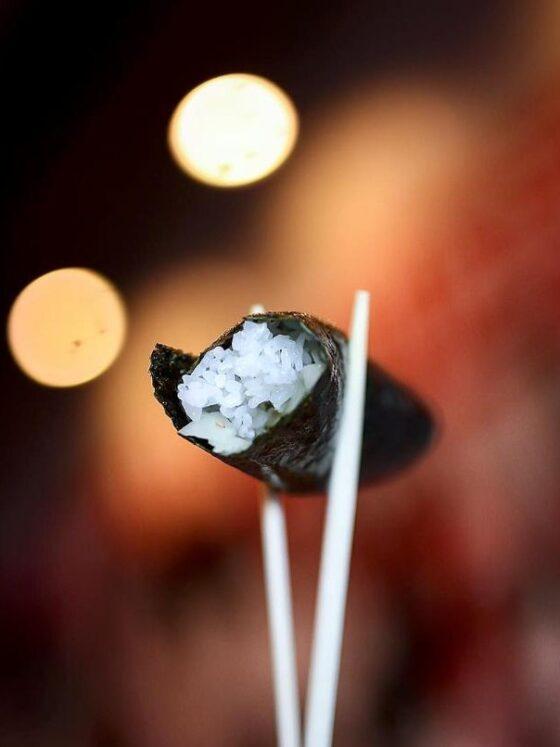 Chopsticks holding up a sushi roll