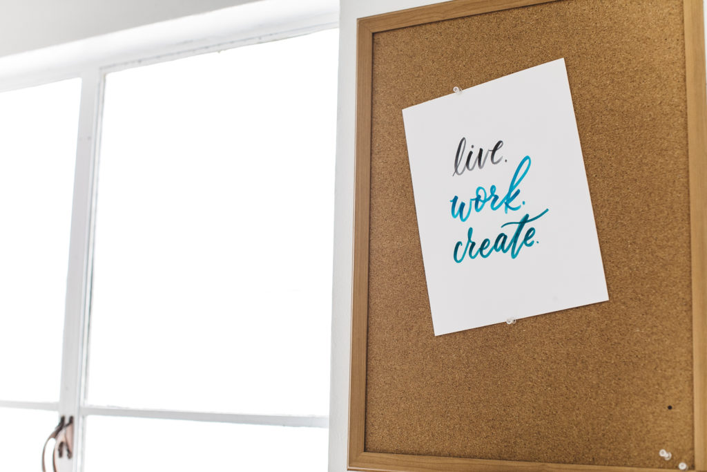 "a sign reading ""Live. Work. Create."" pinned to a cork board."