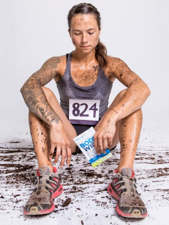 Woman covered in dirt holding a ShowerPill Body Wipe