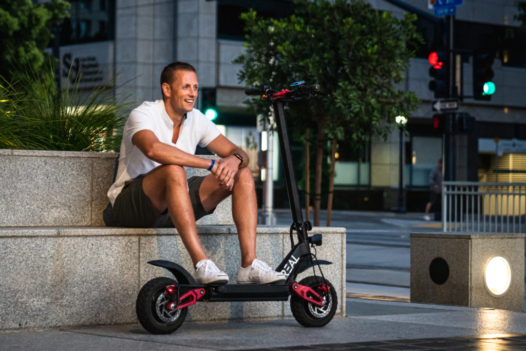 Young man sitting on a bench with his feet resting on a Real Scooter electric scooter.
