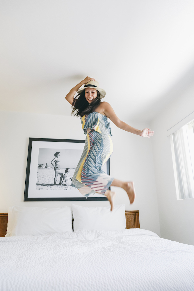 Young woman jumping no the bed at Villa Capri by the Sea.