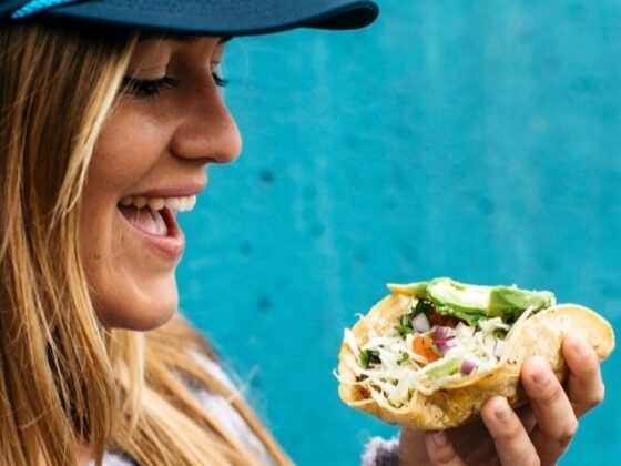 A young woman wearing a Mike's Taco Club Hat eating a taco.