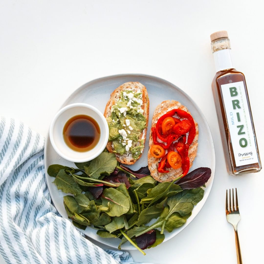 An example of the old Brizo Everything Dressing bottle next to a plate of spinach and toasts.
