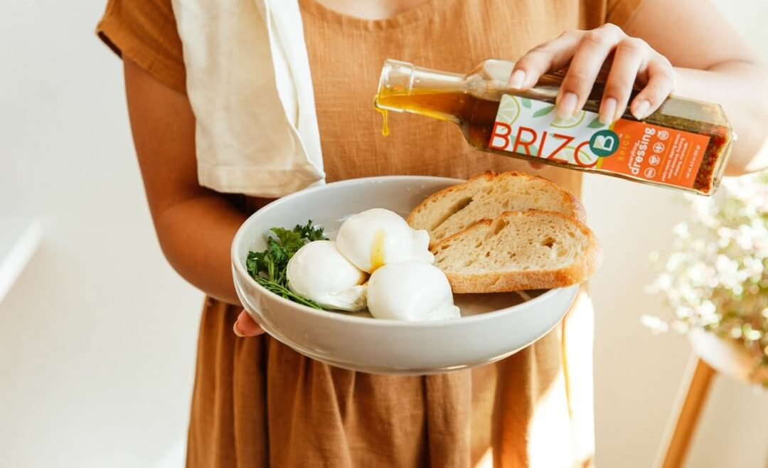 woman pouring Brizo Everything dressing on a bowl of burrata and bread.