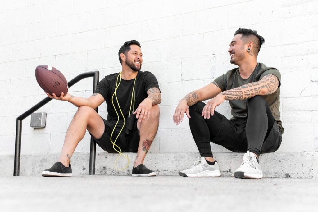 Two guys sitting on step with football